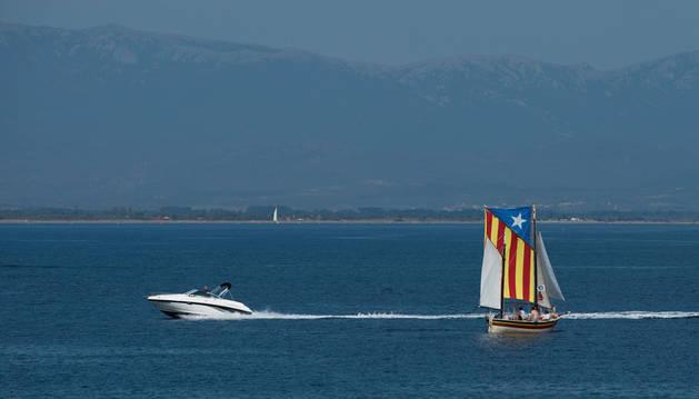 Una lancha rápida pasa por un barco de vela que lleva una