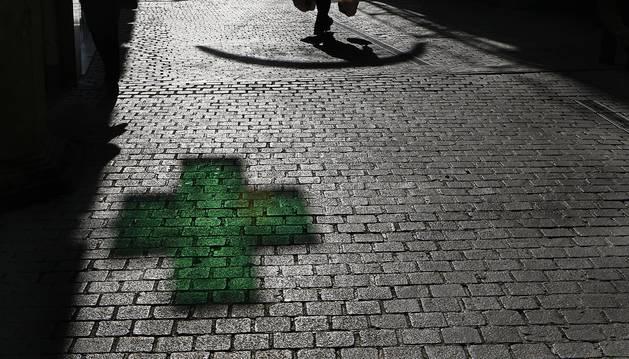 Imagen del reflejo de la cruz de una farmacia.