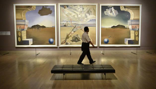 Un hombre pasa delante de una de las obras de Dalí durante la presentación de la exposición en el Centro Nacional de Arte de Tokio.