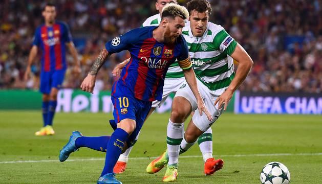 Messi regatea a dos rivales.