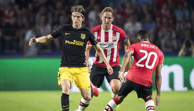 Los jugadores del PSV Eindhoven Luuk de Jong (c) y Joshua Brenet (d) disputan el balón con Filipe Luis (i) del Atlético de Madrid