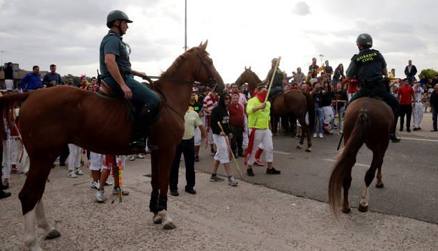 Un hombre sostiene un palo frente a los agentes de la Guardia Civil, antes del comienzo del Toro de la Peña.