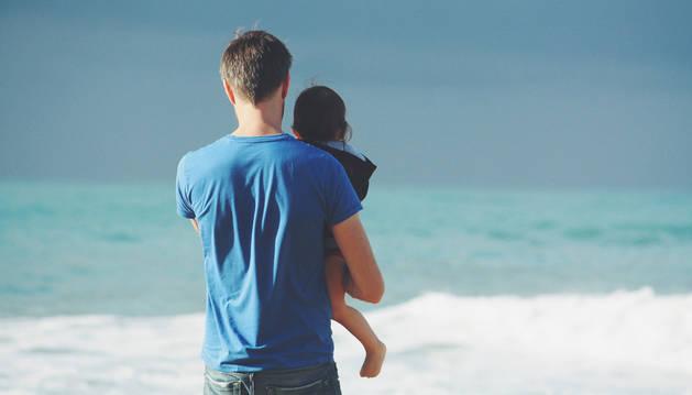 Un padre con su hija en brazos.