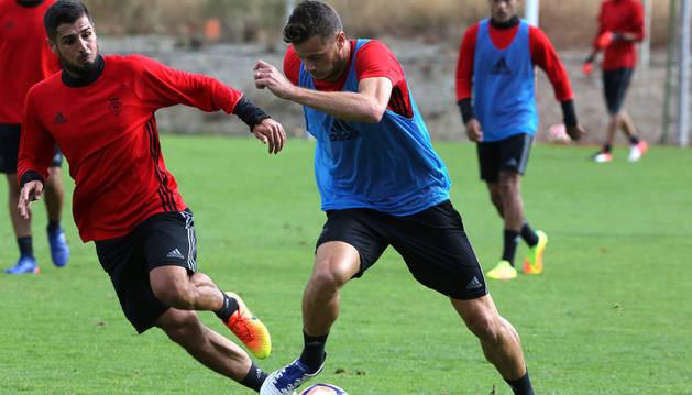 Oriol Riera conduce el balón en presencia de Fran Mérida durante un entrenamiento en Tajonar