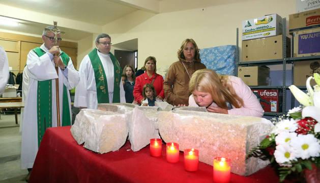 Una mujer besa la cruz rota en el interior de la iglesia de San Blas de Ribaforada.
