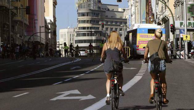 Dos mujeres recorren en bicicleta la Gran Vía de Madrid.