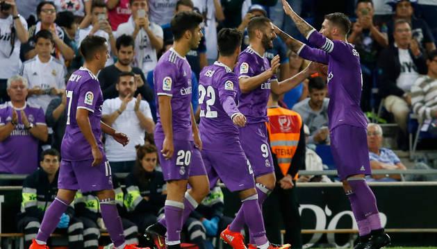 Benzema celebra con sus compañeros de equipo después de anotar durante el partido.