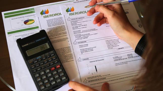 Un cliente revisa una factura con una calculadora.