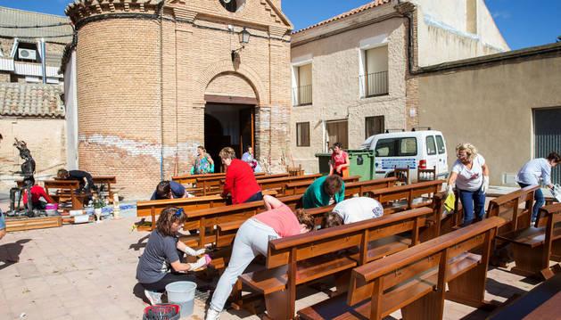 Vecinos de Fontellas limpian los bancos en el exterior de la iglesia con una de las imágenes de la Virgen afectadas, a la izda.