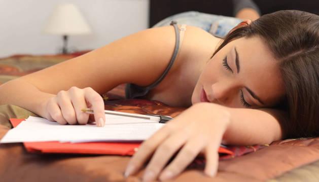 Una joven se duerme mientras estudiaba.