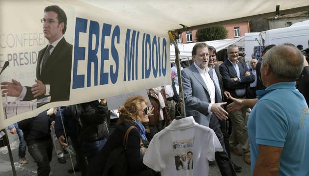 El presidente del Gobierno en funciones, Mariano Rajoy (i), saluda a un vendedor durante el paseo que ha realizado este lunes en la localidad coruñesa de Santa Comba.