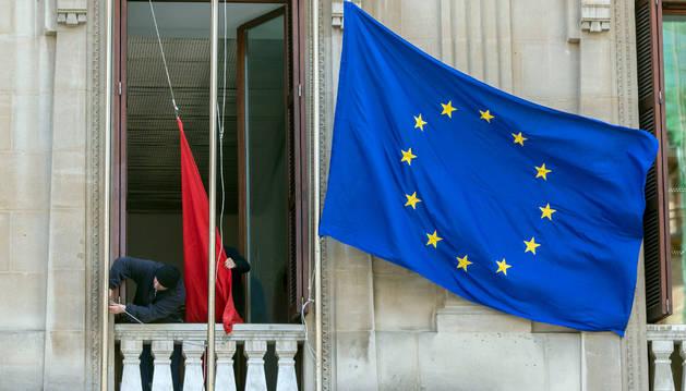 Los operario vuelven a colocar la bandera europea en el Parlamento de Navarra.
