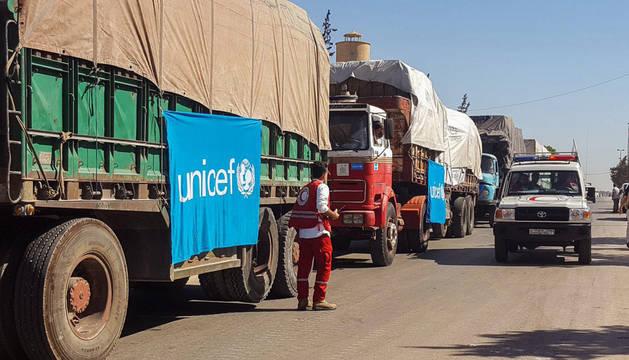 Fotografía cedida por la Media Luna Roja Siria que muestra un convoy de camiones antes de partir para entregar ayuda humanitaria.