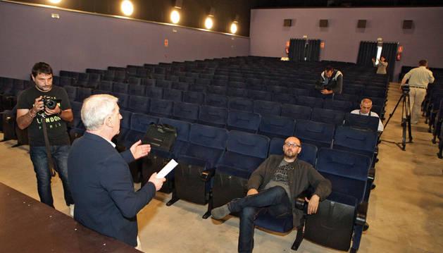 El concejal Javier Gómez, de espaldas, explica en el cine Moncayo las mejoras que se han llevado a cabo.