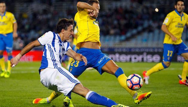 El delantero de la Real Sociedad, Mikel Oyarzabal (i), golpea el balón ante el defensa de la UD Las Palmas, Dani Castellano.