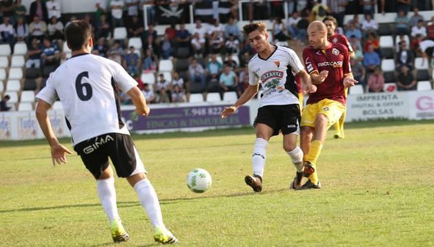 Lizarraga toca un balón hacia un compañero ante la presión de un jugador visitante.