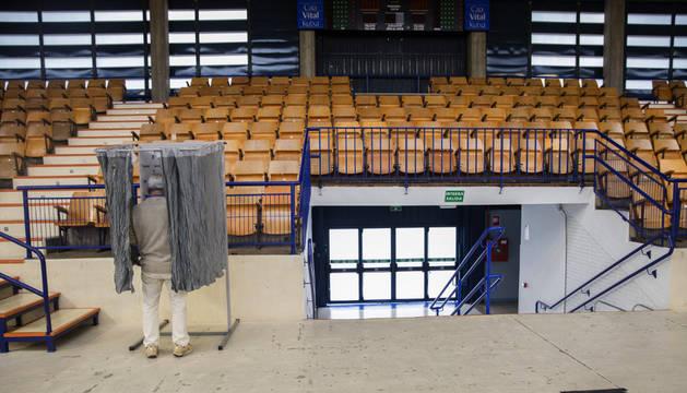 Un hombre elige la papeleta el colegio electoral habiltado en el polideportivo Mendizorrotza de Vitoria.