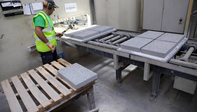Un operario de PVT completa uno de los pasos del proceso de producción de las baldosas ecoGranic.