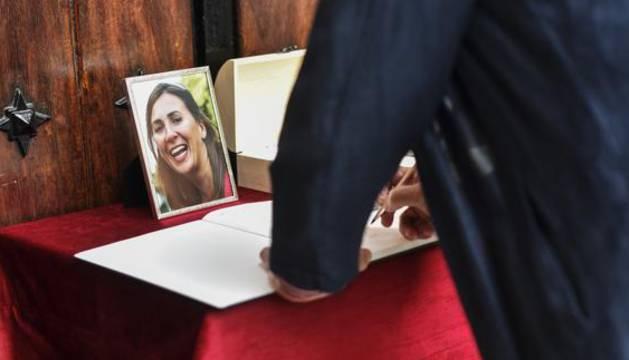 Un hombre firma en el libro de condolencias durante el funeral de María Villar.