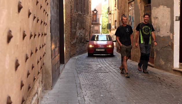 Varias personas pasean por la calle Verjas, con un coche al fondo.