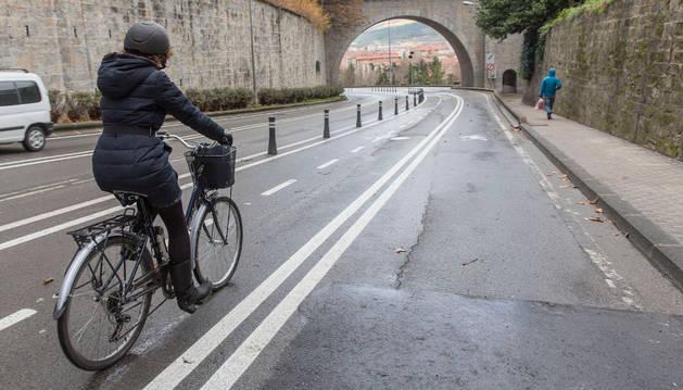 Una mujer circula hacia la Rochapea por el Portal Nuevo,  en un carril que el Ayuntamiento habilitó para bicicletas.