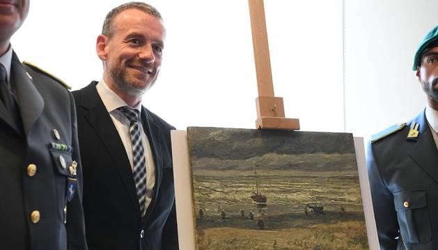 El director del museo Van Gogh, permanece junto a una de las pinturas del artista Vincent Van Gogh