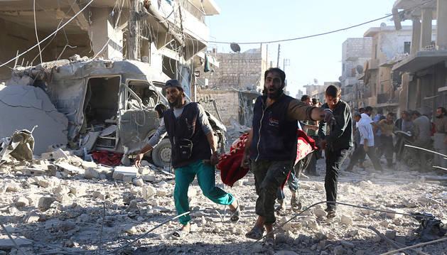 Voluntarios trasladan a un herido en el bombardeo de Alepo.