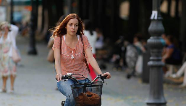 Una joven pasea en bicicleta por Pamplona.