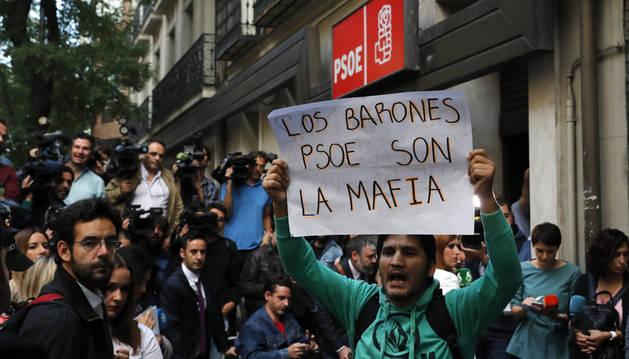 Un simpatizante muestra una pancarta a las puertas de la sede del PSOE, en la madrileña calle Ferraz.