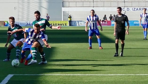El delantero almeriense del Izarra, Pito, es derribado dentro del área por dos jugadores del Coruxo.
