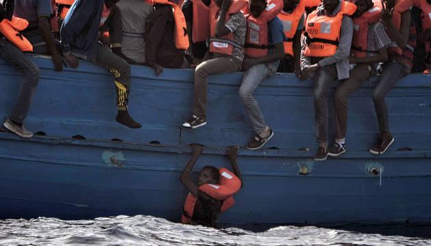 Un inmigrante, colgado de una lancha a 20 millas de la costa de Libia.