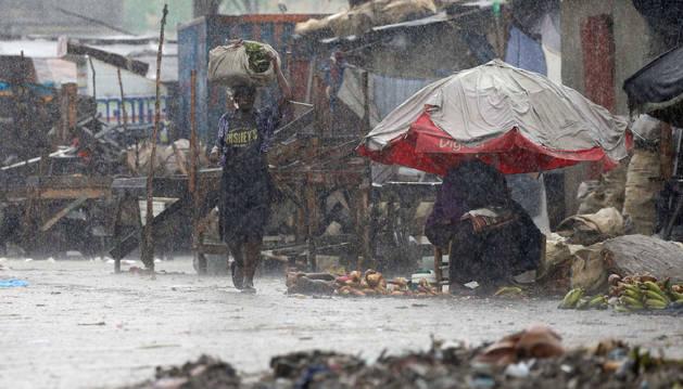 Una mujer camina por la calle mientras el huracán Matthew pasa por Puerto Príncipe.