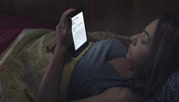 Una joven lee un libro electrónico.