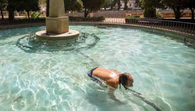 Un joven disfruta de un baño en una fuente en Granada.