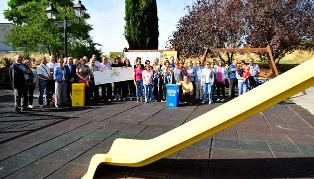 Imagen de autoridades y vecinos de Mañeru posan con el cheque que escenifica el premio en el parque infantil que se arreglará con el dinero ganado.