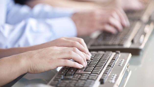 Varios hombre teclean en un ordenador.