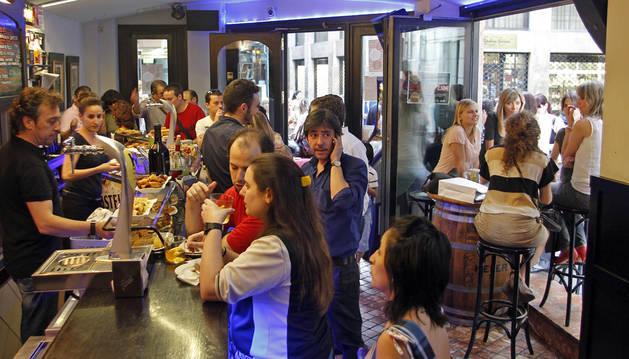 Decenas de personas disfrutan de un momento de ocio en una jornada de juevintxo en Pamplona.