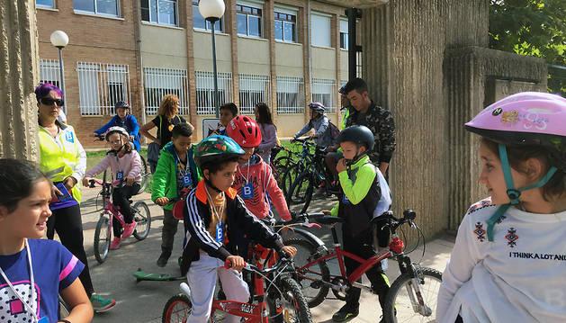 Un grupo de alumnos sale del colegio con sus bicicletas o patinetes.
