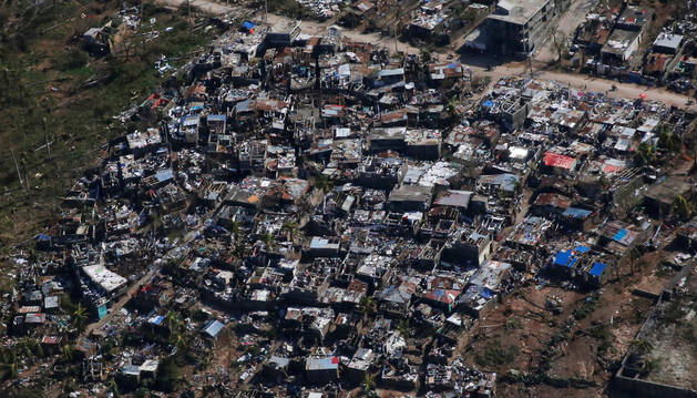 La gente camina por una calle junto a las casas destruidas tras el huracán Mateo en Jeremie, Haití.