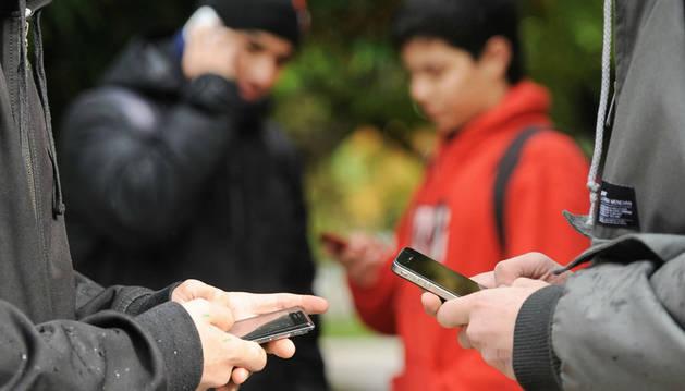 Jóvenes consultan su teléfono móvil.
