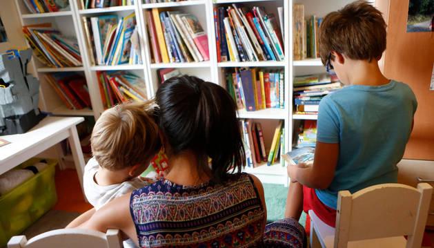 Una madre lee cuentos infantiles a sus dos hijos, en una habitación de su casa.