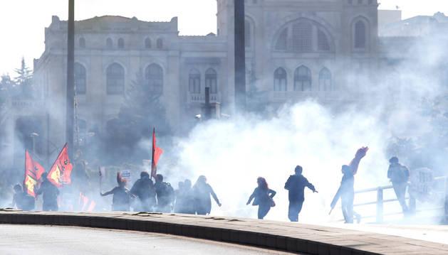 Varios manifestantes dispersándose tras el uso de gases lacrimógenos por parte de la policía.