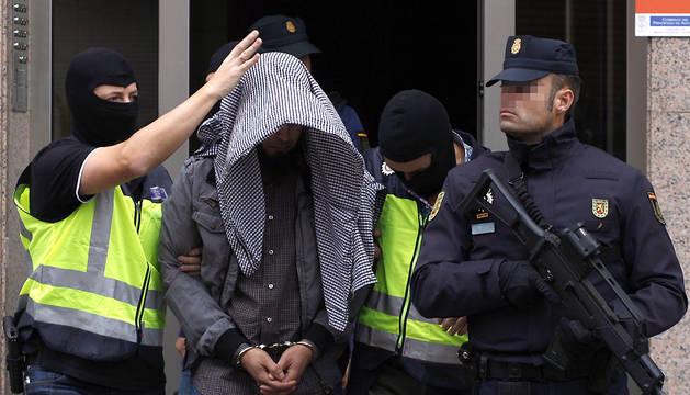 Agentes del Cuerpo Nacional de Policía trasladan a un hombre de orígen marroquí, que ha sido detenido en Gijón.