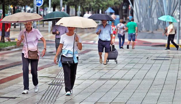 Imagen de varias personas con paraguas en la calle Irunlarrea de Pamplona.