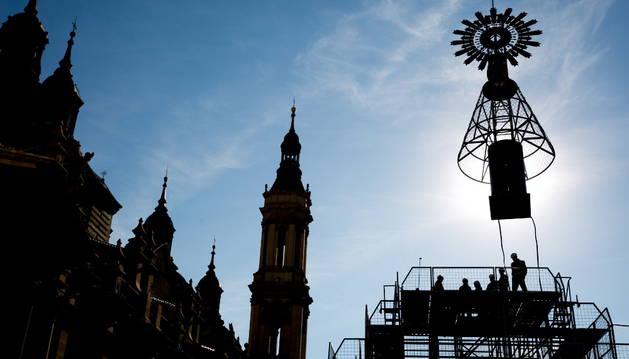 Operarios municipales preparan la imagen de la Virgen del Pilar para ser colocada con una grúa sobre la estructura instalada ante su Basílica para la Ofrenda de Flores.
