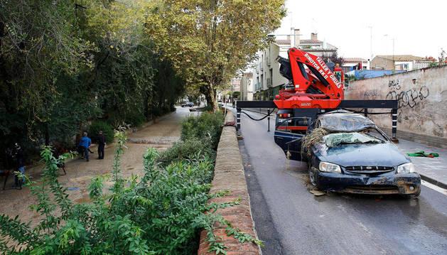 Una grúa retira el vehículo del hombre que falleció al ser arrastrado por el agua en una riera de Vilassar de Mar (Barcelona).