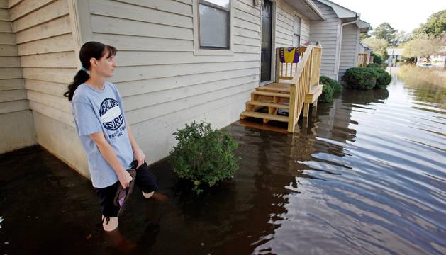 Un mujer espera junto a su casa la llegada de ayuda tras el paso del huracán Matthew por Carolina del Norte.