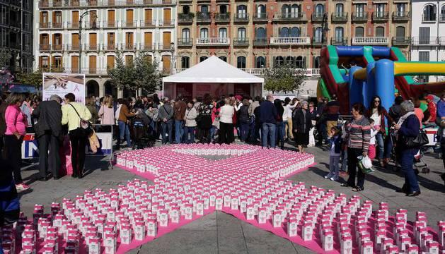 Una gran lazo rosa elaborado con cajas de leche junto a la carpa informativa.