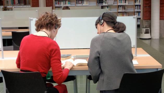 La voz susurrante ha pedido a una de las participantes que guíe con su dedo a la otra en la lectura de uno de los libros.