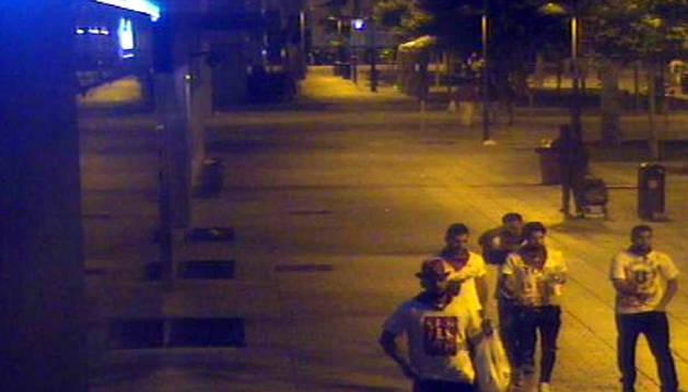 Foto de procesados caminan por la calle Roncesvalles de Pamplona tras haber salido del portal de Paulino Caballero, donde dejaron a la joven.